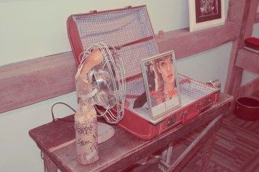 Framed vintage ads, suitcases, fans set the scene